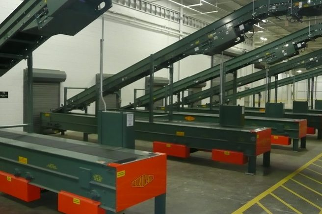 Automated conveyor rack system at point of exit to truck area